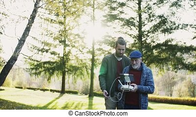 Senior father and his young son with drone in nature, talking.
