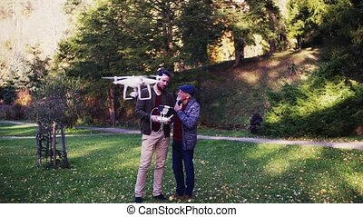 Senior father and his son with drone in nature, talking....