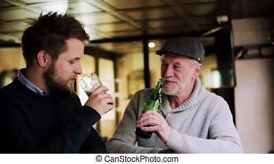 Senior father and his young son drinking beer in a pub.