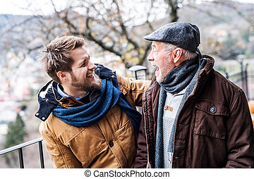 Senior father and his young son on a walk. - Senior father ...