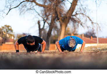 Senior father and son doing pushups outdoors