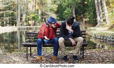 Senior father comforting his sad adult son on bench by lake...