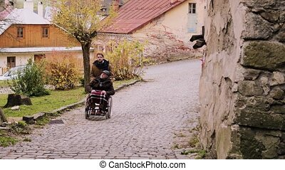 Senior father in wheelchair and young son on a walk. -...