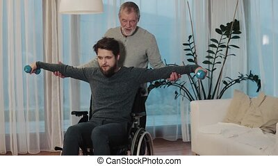 Senior father with hipster son in wheelchair at home.