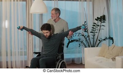 Senior father with hipster son in wheelchair at home. -...