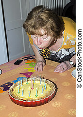 senior female blows out candles on a cake