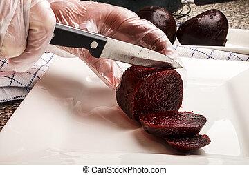 senior female chef cutting beetroot