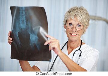 Senior Female Doctor Holding Hip Xray Report