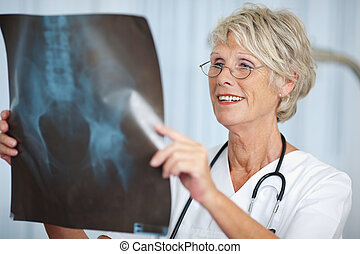 Senior Female Doctor Looking At Hip Xray Report - Portrait...