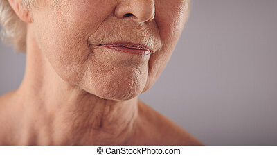 Senior female face with wrinkled skin