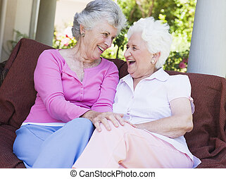 Senior female friends chatting together sitting on garden ...