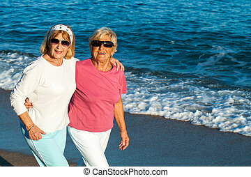 Senior female friends walking along the beach. - Portrait of...