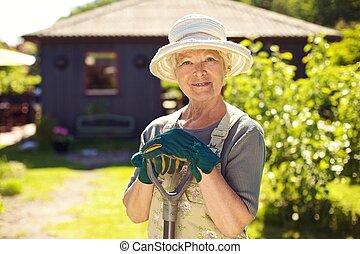 Senior female gardener in backyard with shovel