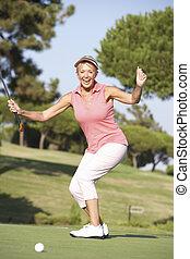 Senior Female Golfer On Golf Course Lining Up Putt On Green