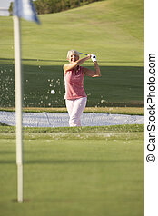 Senior Female Golfer Playing Bunker Shot On Golf Course
