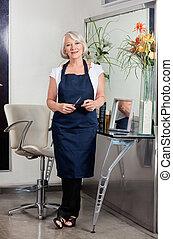 Senior Female Hairdresser Standing At Salon