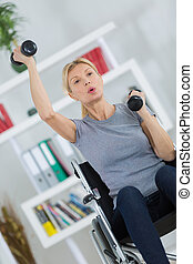 senior female patient in lifting dumbbell in clinic