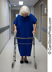 Senior female patient walking with walker in clinic