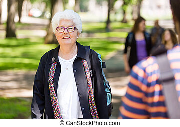 Senior Female Professor Standing On Campus