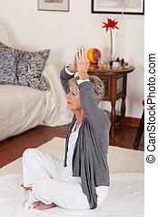 Senior female raising her hands above head