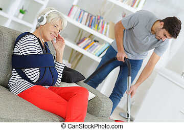senior female sitting on sofa while home help is cleaning