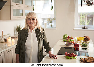 Senior female standing in kitchen with smile