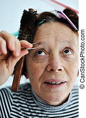 Senior female tweezing eyebrow