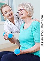 Senior Female Working With Physiotherapist