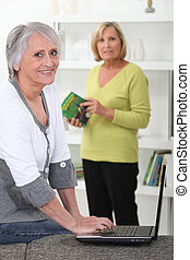 senior females at home with laptop
