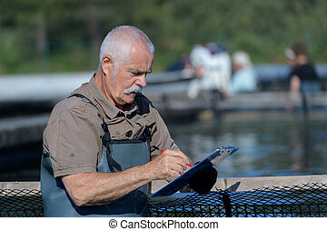 senior fish farmer checking his clipboard