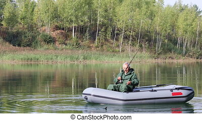Senior fishing in a boat - Senior fisherman floats on a lake...