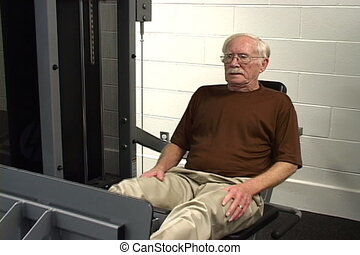 Senior citizen works his legs muscles on a gym machine.