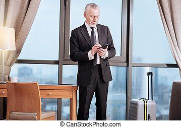 Senior focused man  checking his calls