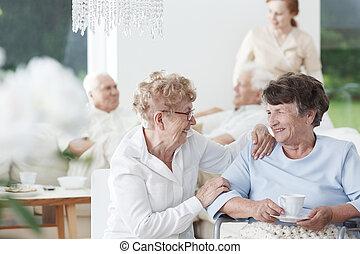 Senior friends laughing - Two senior women friends talking...