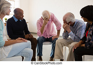 Senior friends looking at man with head in hand