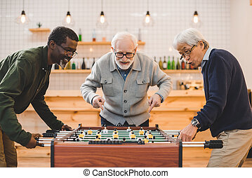 senior friends playing kicker - multiethnic group of senior...