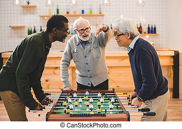 senior friends playing table football - group of handsome...