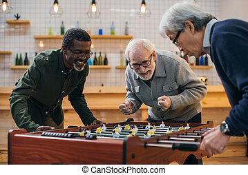 senior friends playing table football - group of senior...