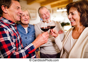 Senior friends with champagne at Christmas time.