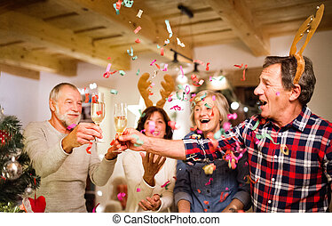Senior friends with confetti and champagne at the Christmas...
