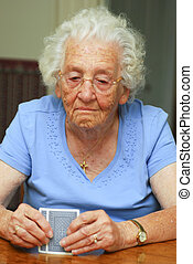 Senior woman holding cards looking at them with thoughtful expression