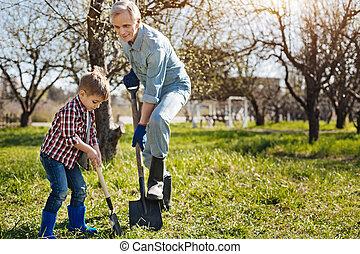 Senior gardener and his grandson digging ground together