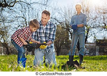 Senior gardener watching his son and grandchild setting tree