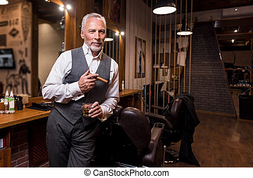 Senior gentleman standing with glass and cigar