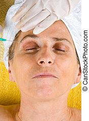 Senior  getting  botox injection in eyebrow