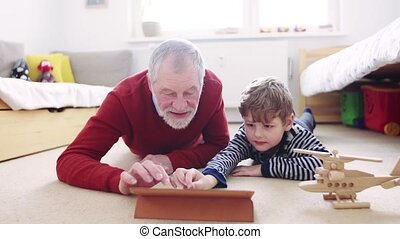 Senior grandfather and a small grandson with tablet playing at home.
