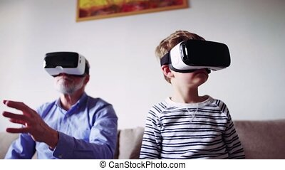 Senior grandfather and a small grandson with VR goggles at home.