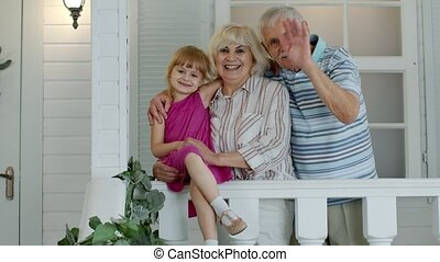 Happy senior grandfather and grandmother couple with granddaughter waving hand, smiling, saying hello in porch at home. Mature lifestyle family concept. Grandparens with young child girl. 6k downscale