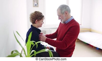 Senior grandfather buttoning up a shirt of small grandson at...