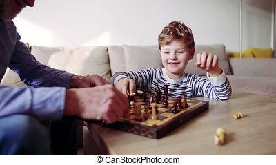 Senior grandfather with a grandson playing chess at home. -...